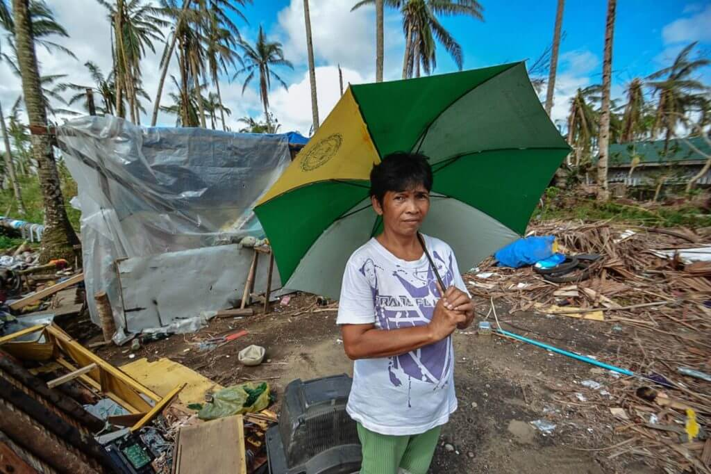 Man holding umbrella stands in front of damage caused by Hurricane Maria.
